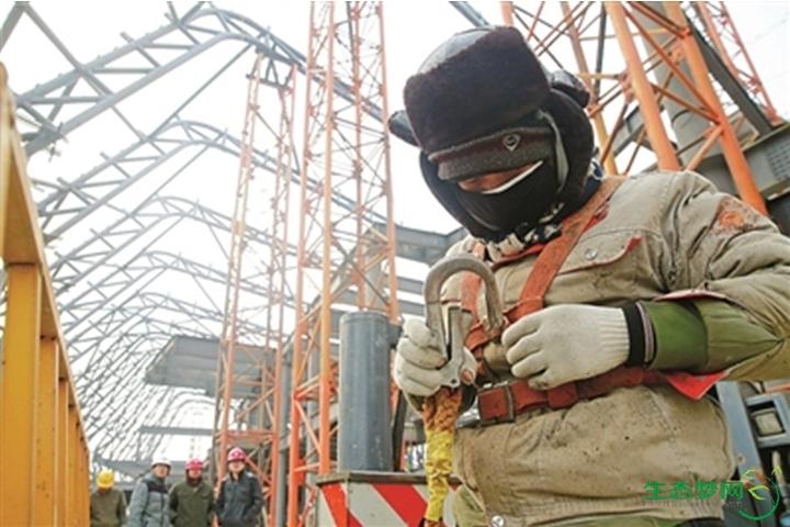 """一根根银灰色的巨大钢结构桁架已经搭建起来,几名焊工像""""蜘蛛人""""一样"""